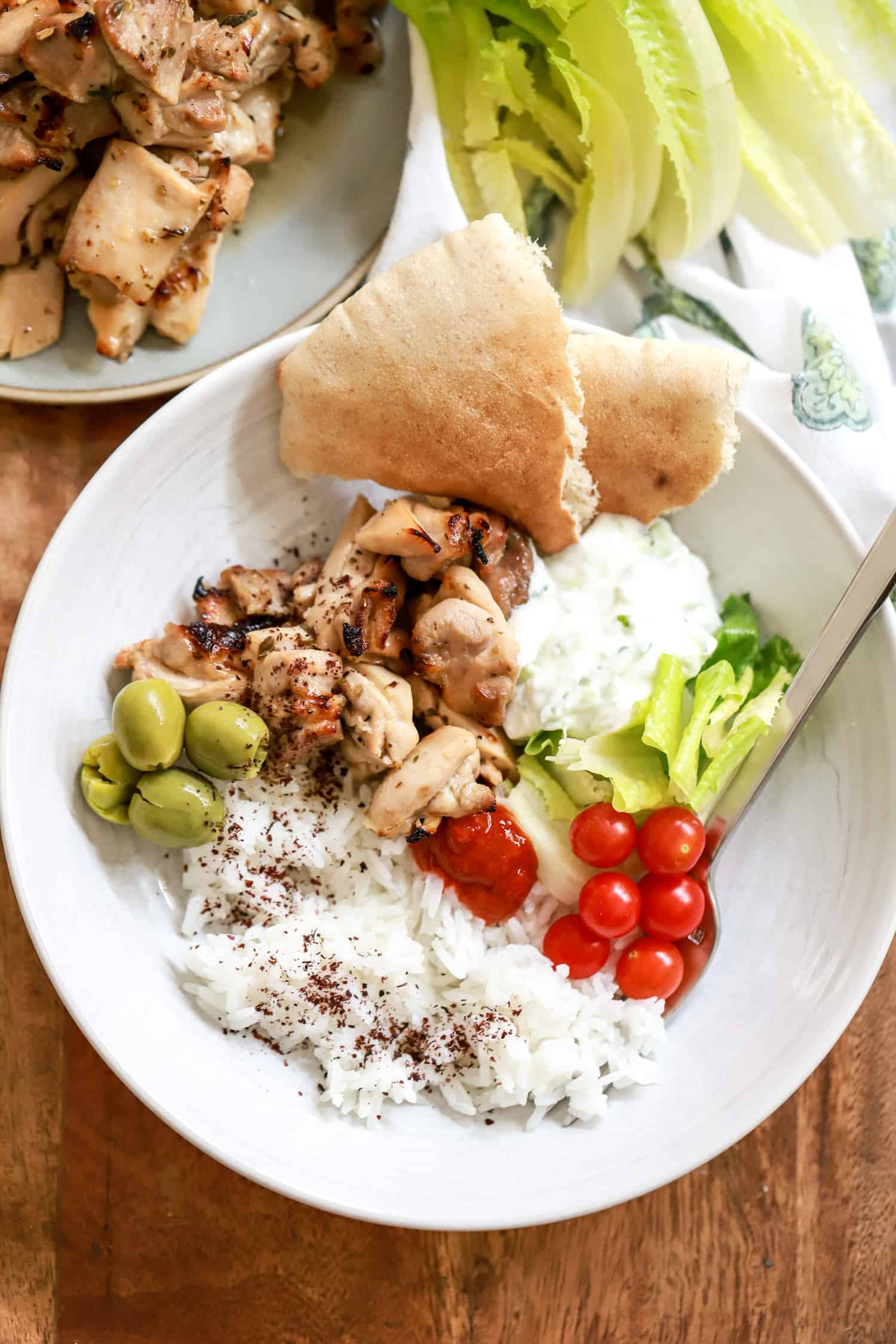 white bowl with rice, chicken pieces, tomatoes, olives, and lettuce leaves with pita on the side.