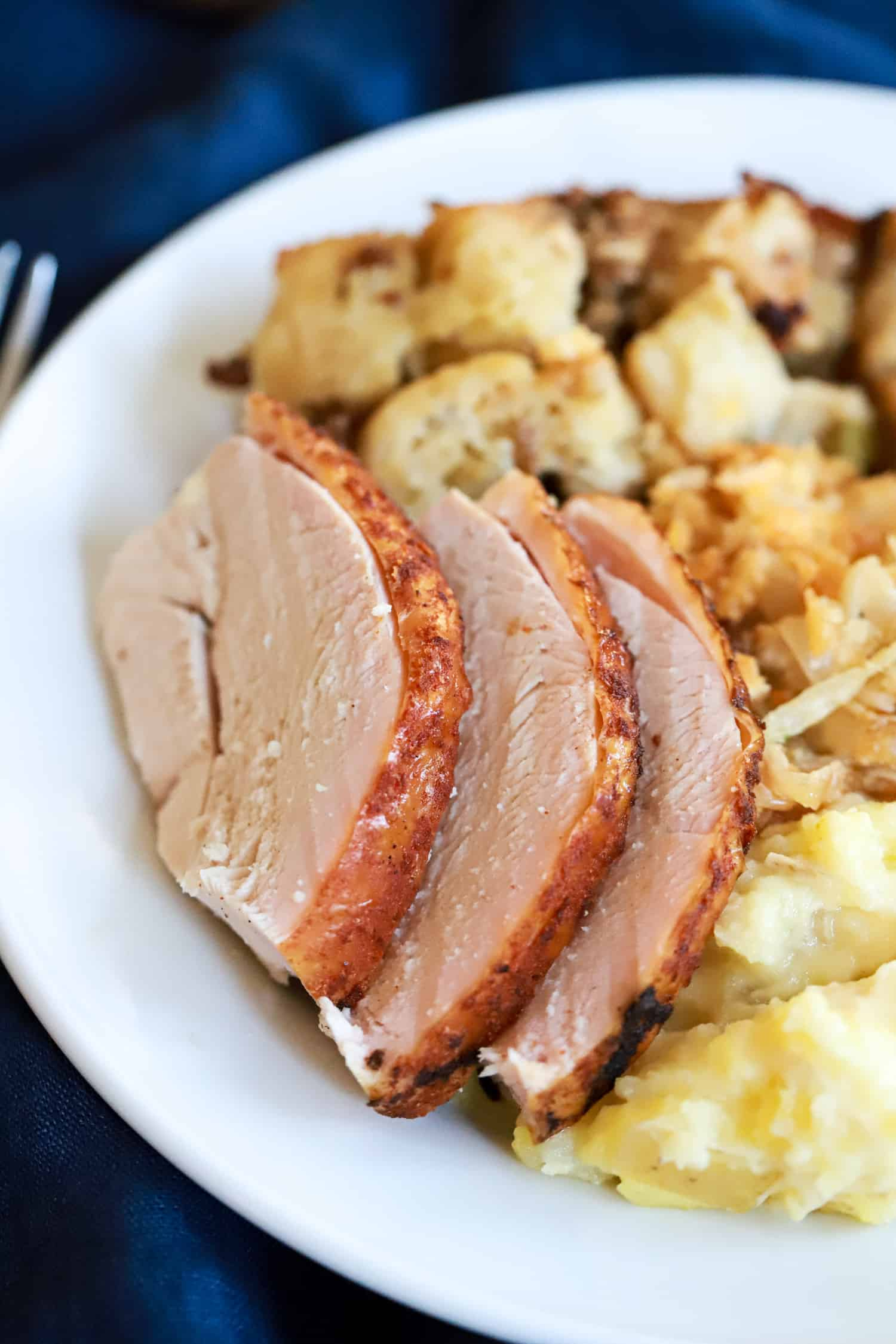 slices of turkey on a white plate with thanksgiving side dishes.