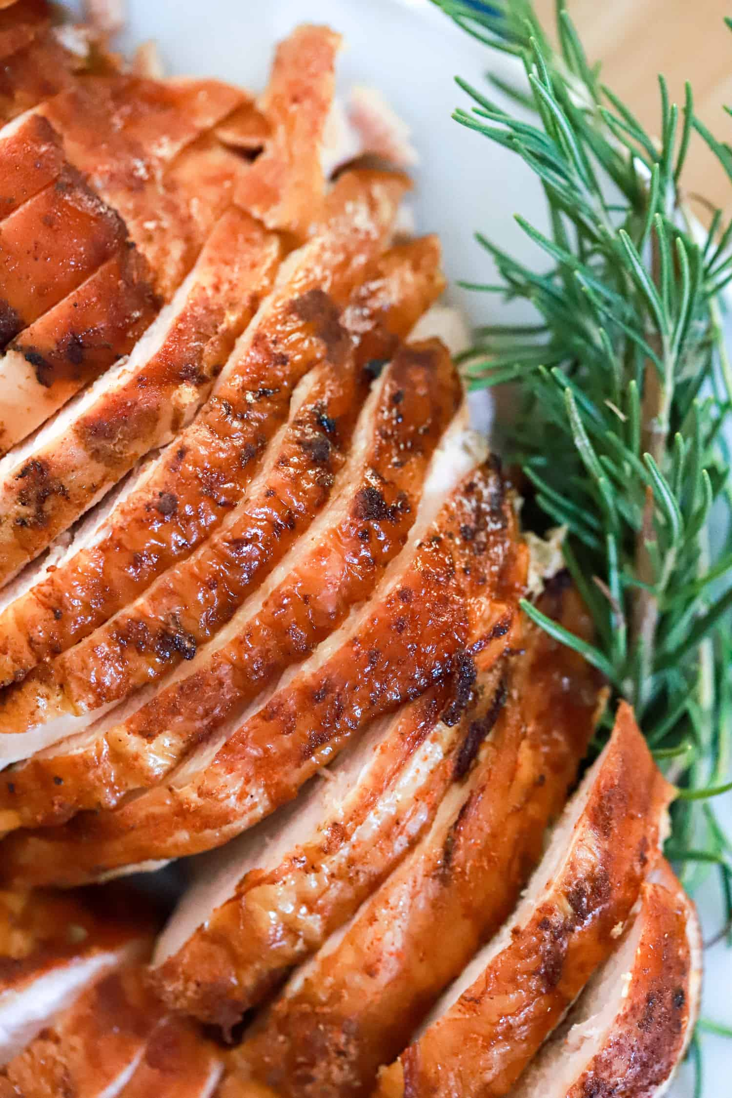 close up of sliced turkey with fresh rosemary sprig on the side.