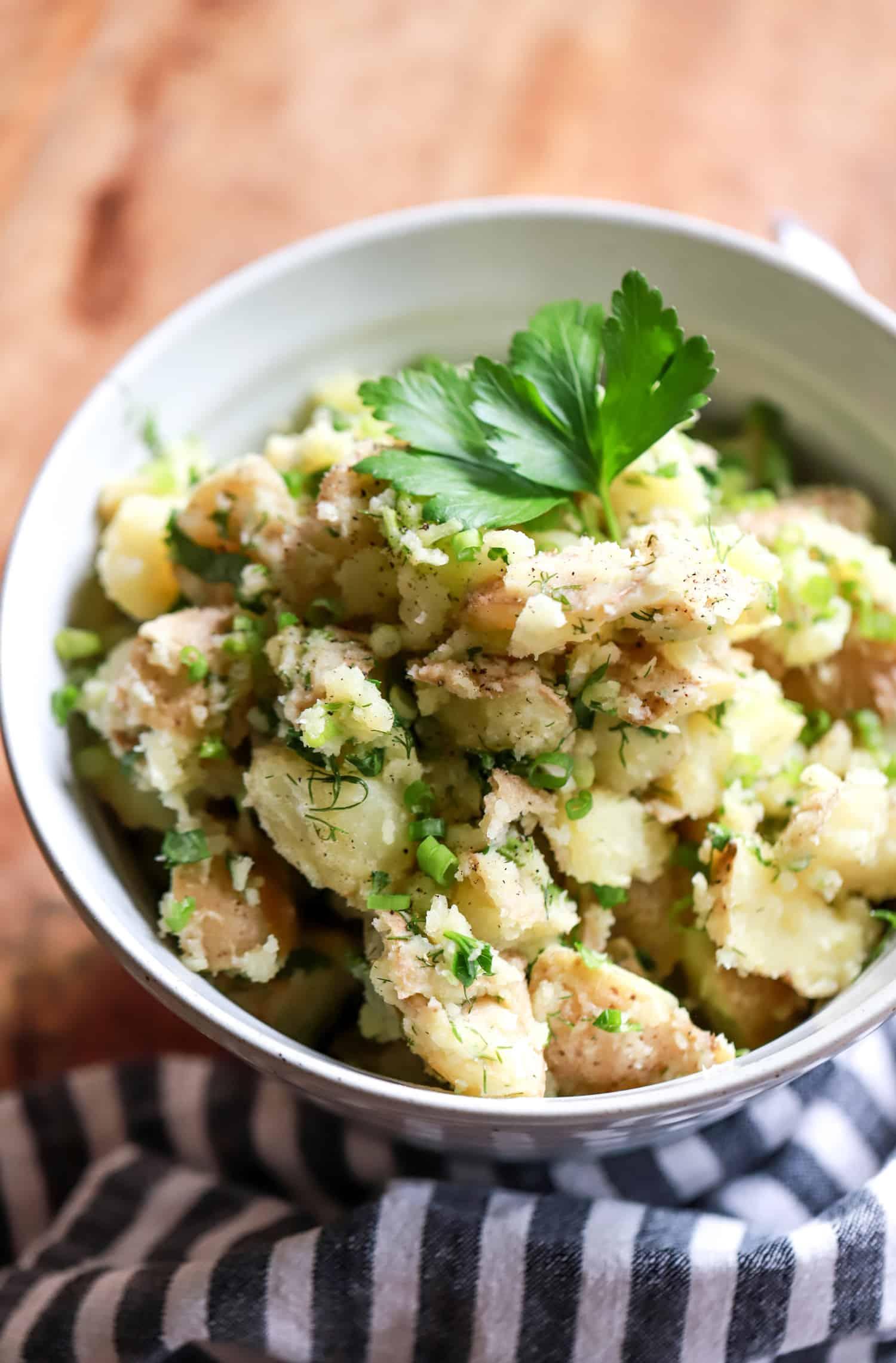 vegan potato salad in a bowl with striped napking