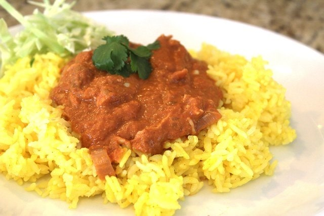 Spoon curry over rice