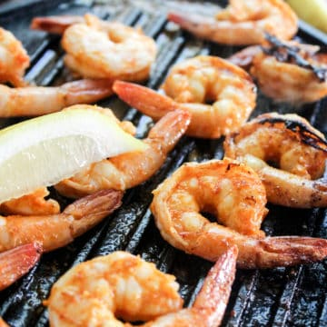 cooked grilled shrimp on grill pan with lemon slices