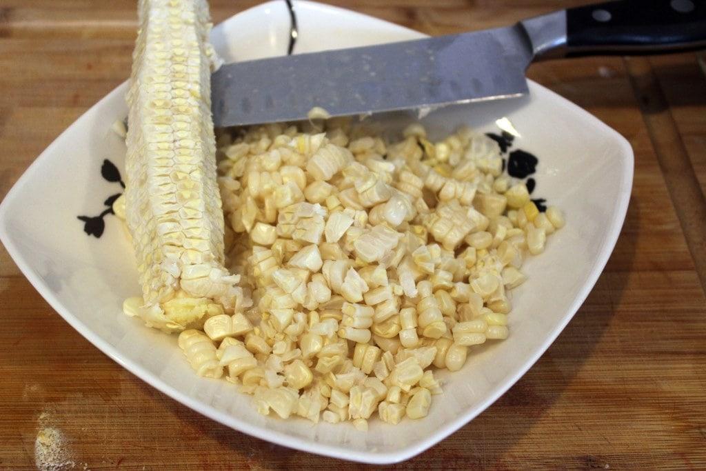 Scrape corn from cob