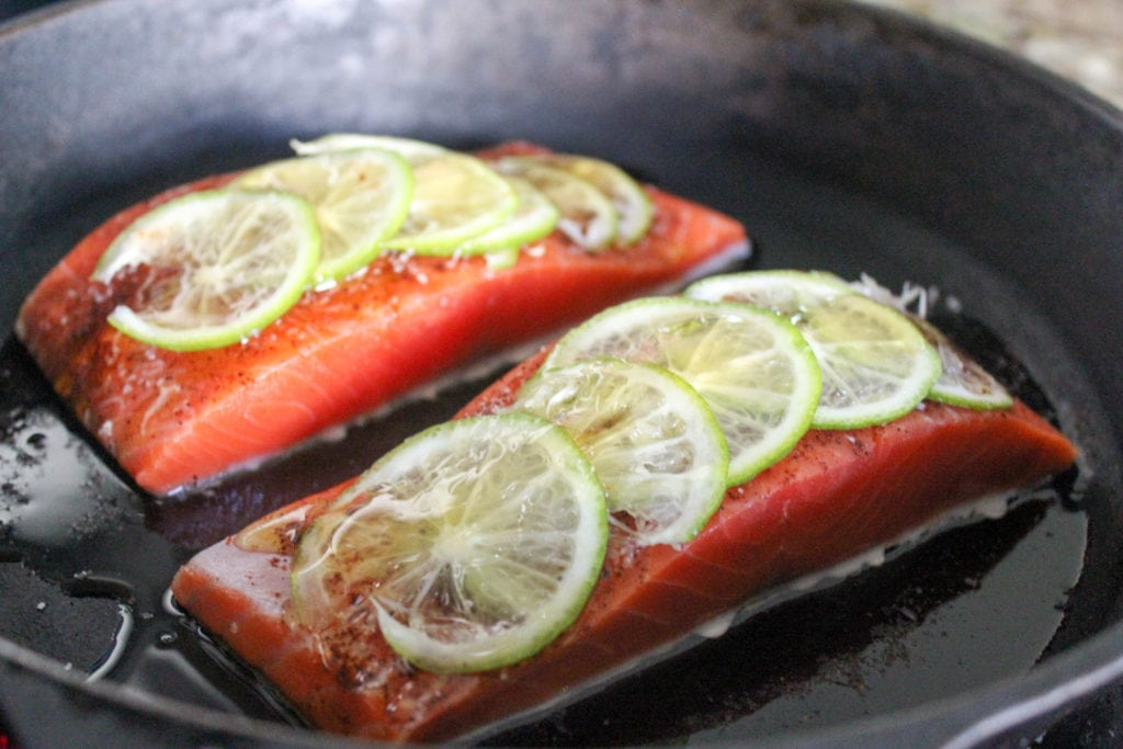 salmon cooking in cast iron skillet
