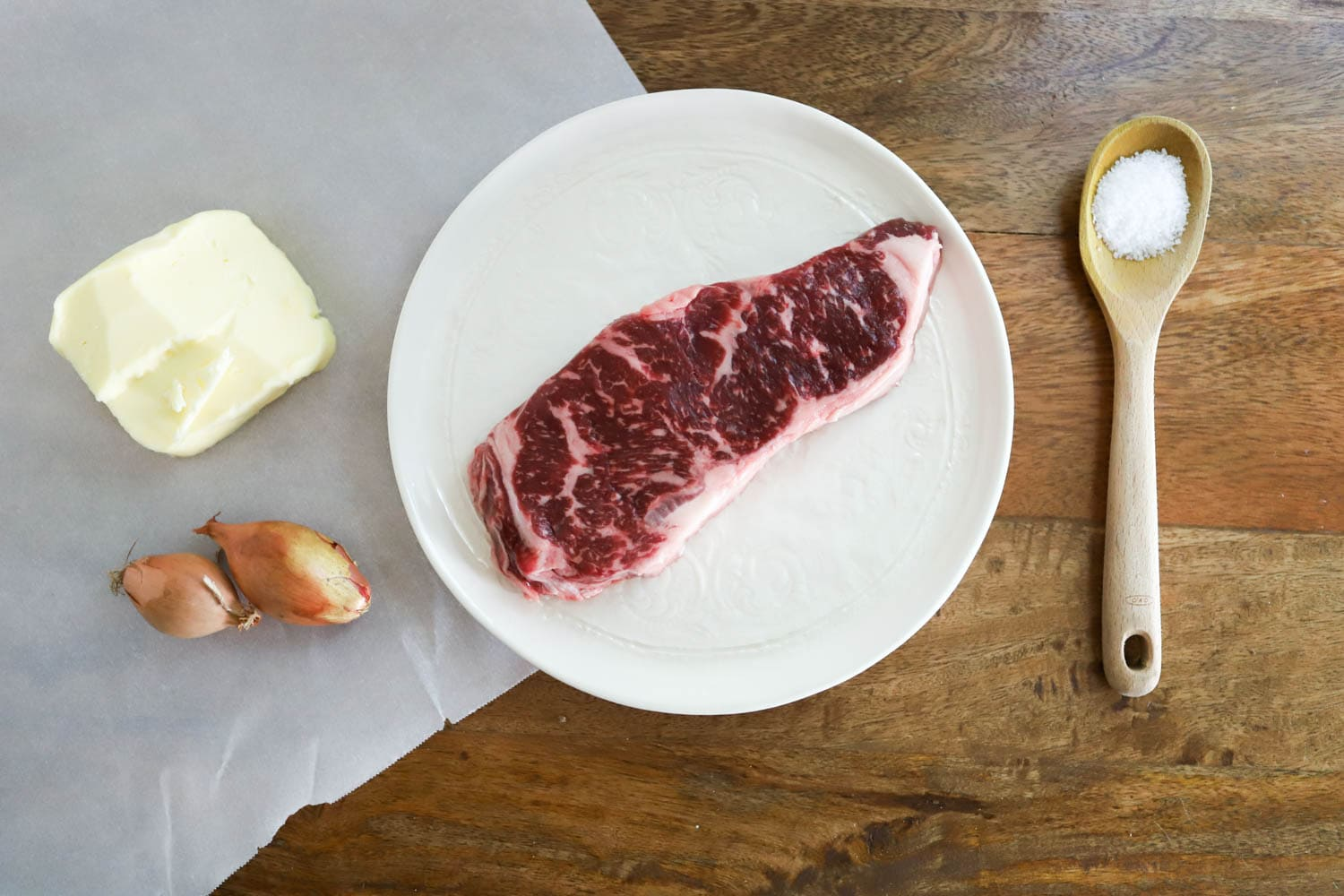 ingredients for ny strip steak on wooden board with parchment paper.