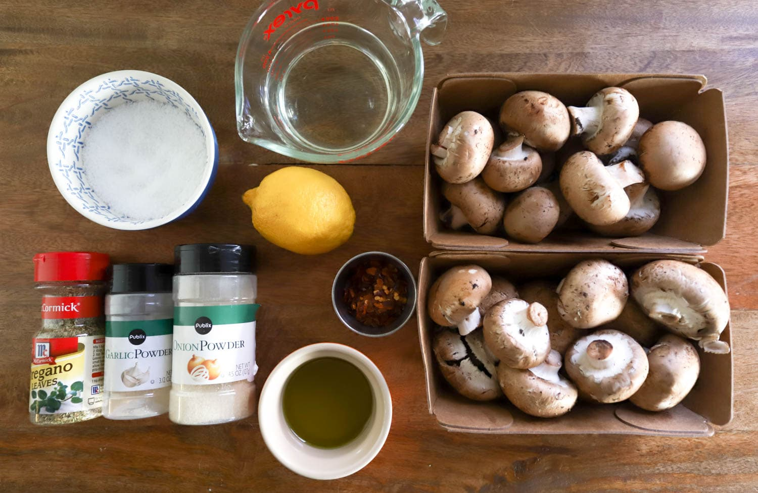 ingredients for marinated mushrooms over brown wooden board.