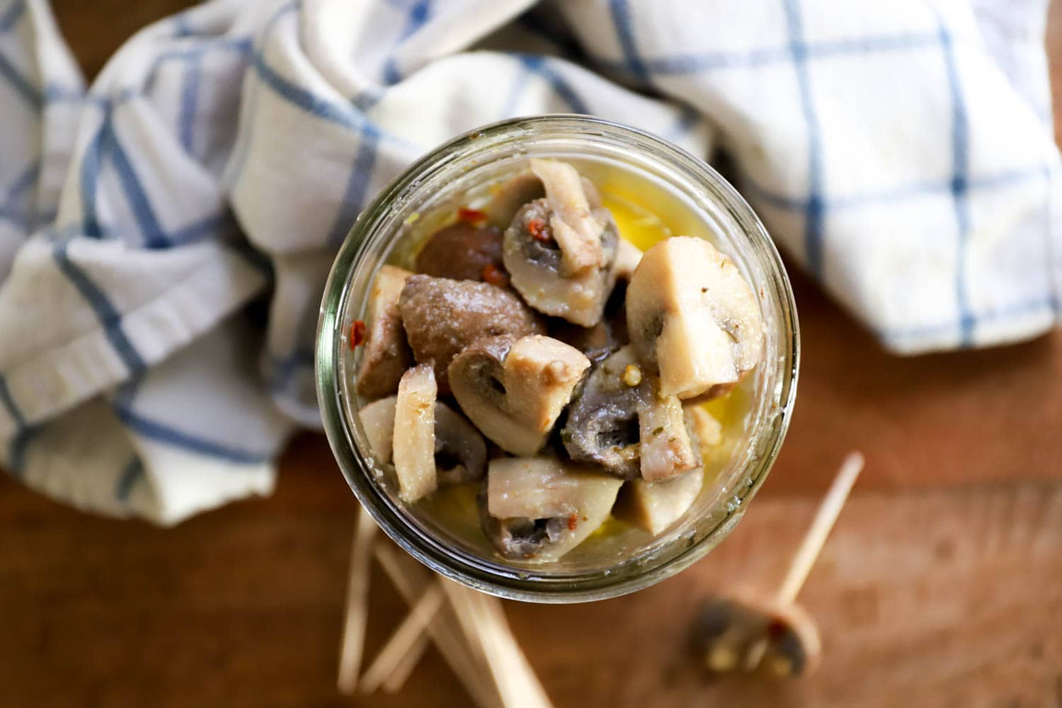jar of pickled raw mushrooms with a blurry napkin in the background.