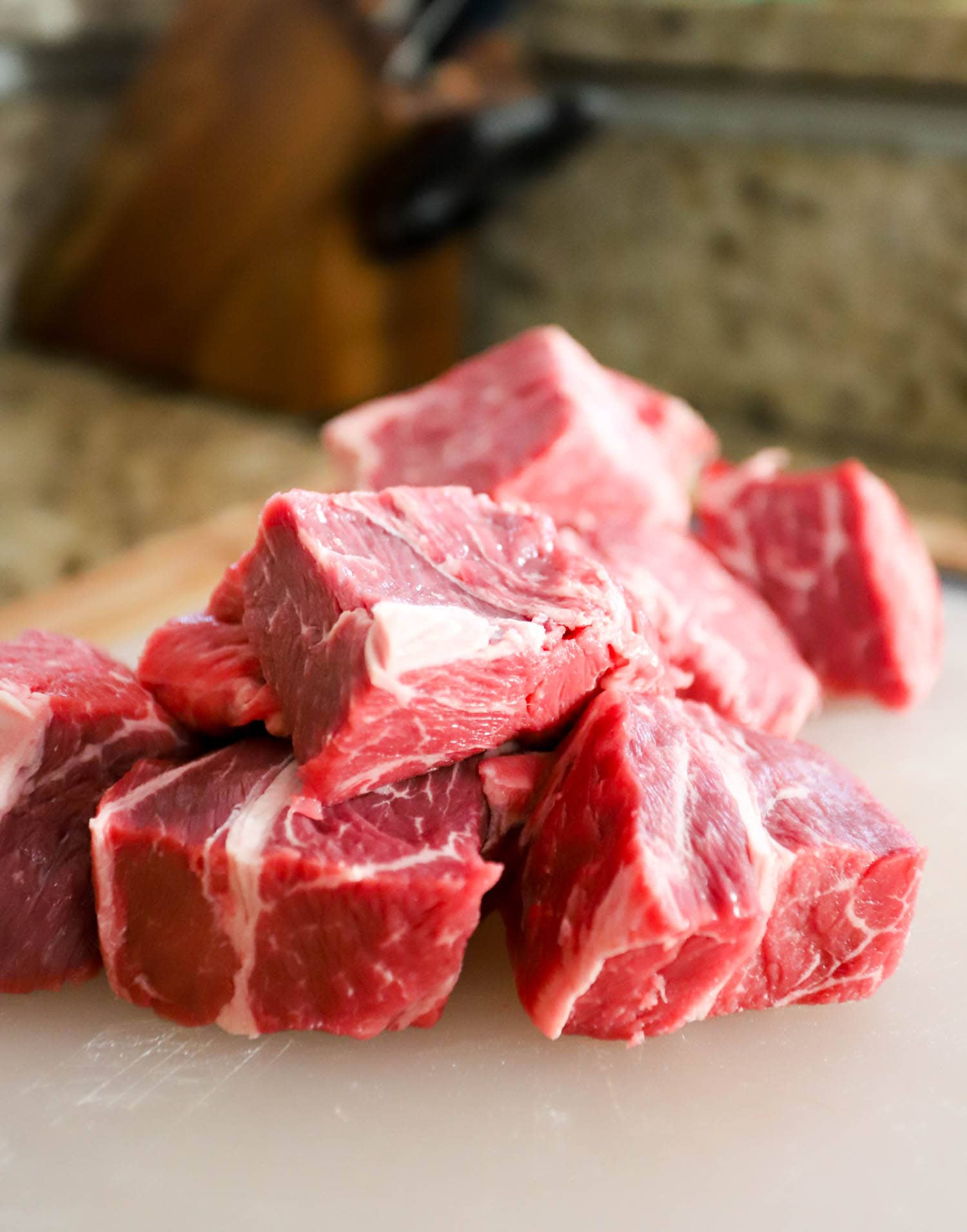 large chunks of beef cut, close up detail shown with granite counter in background.