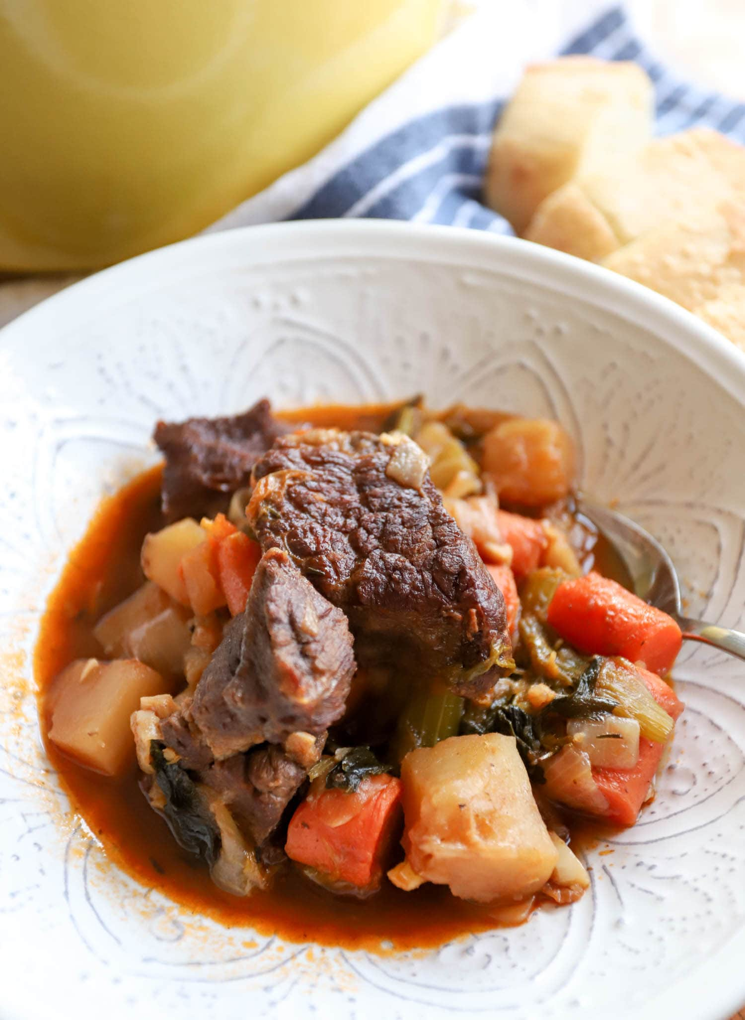 white bowl with beef stew, potatoes, and carrots in front of a yellow dutch oven.