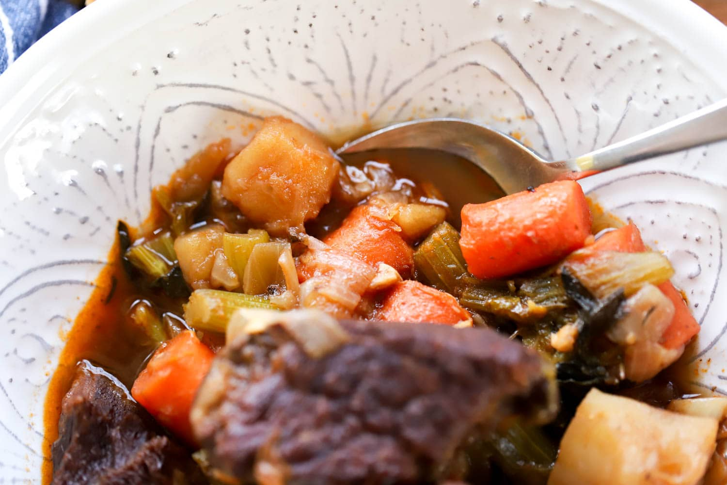 spoon in broth of beef stew with carrots and celery in a white bowl.