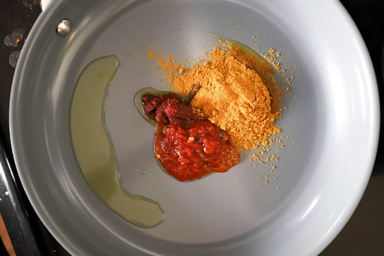 skillet with curry powder, olive oil, and tomato paste