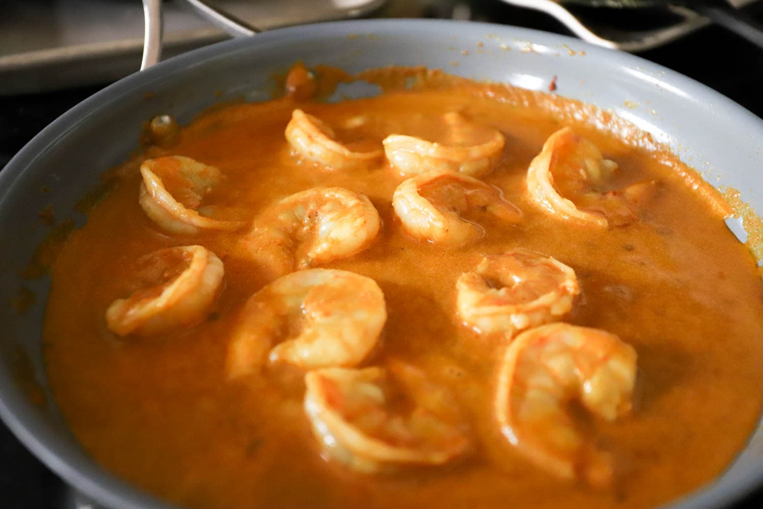 shallow skillet side view with shrimp and curry