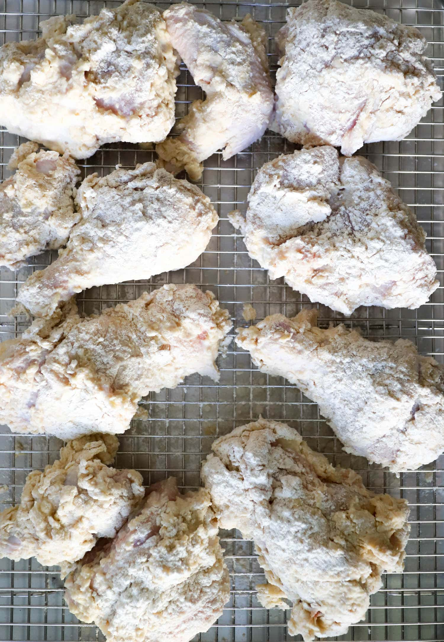uncooked battered chicken on wire baking rack