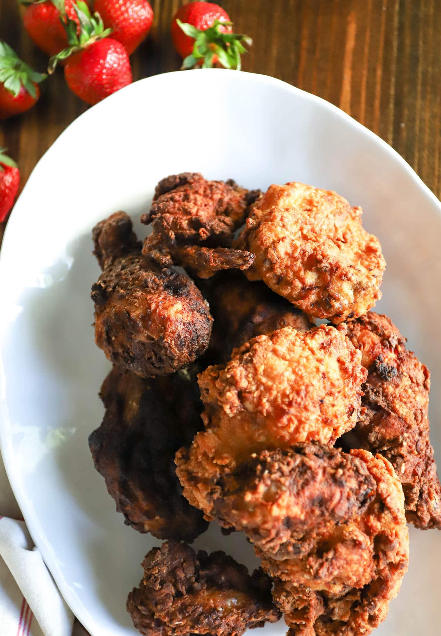 platter of buttermilk fried chicken golden brown with strawberries