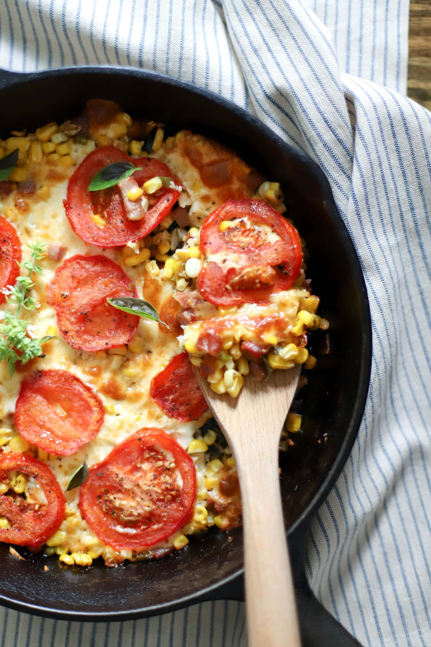 skillet of tomatoes and corn with wooden spoon