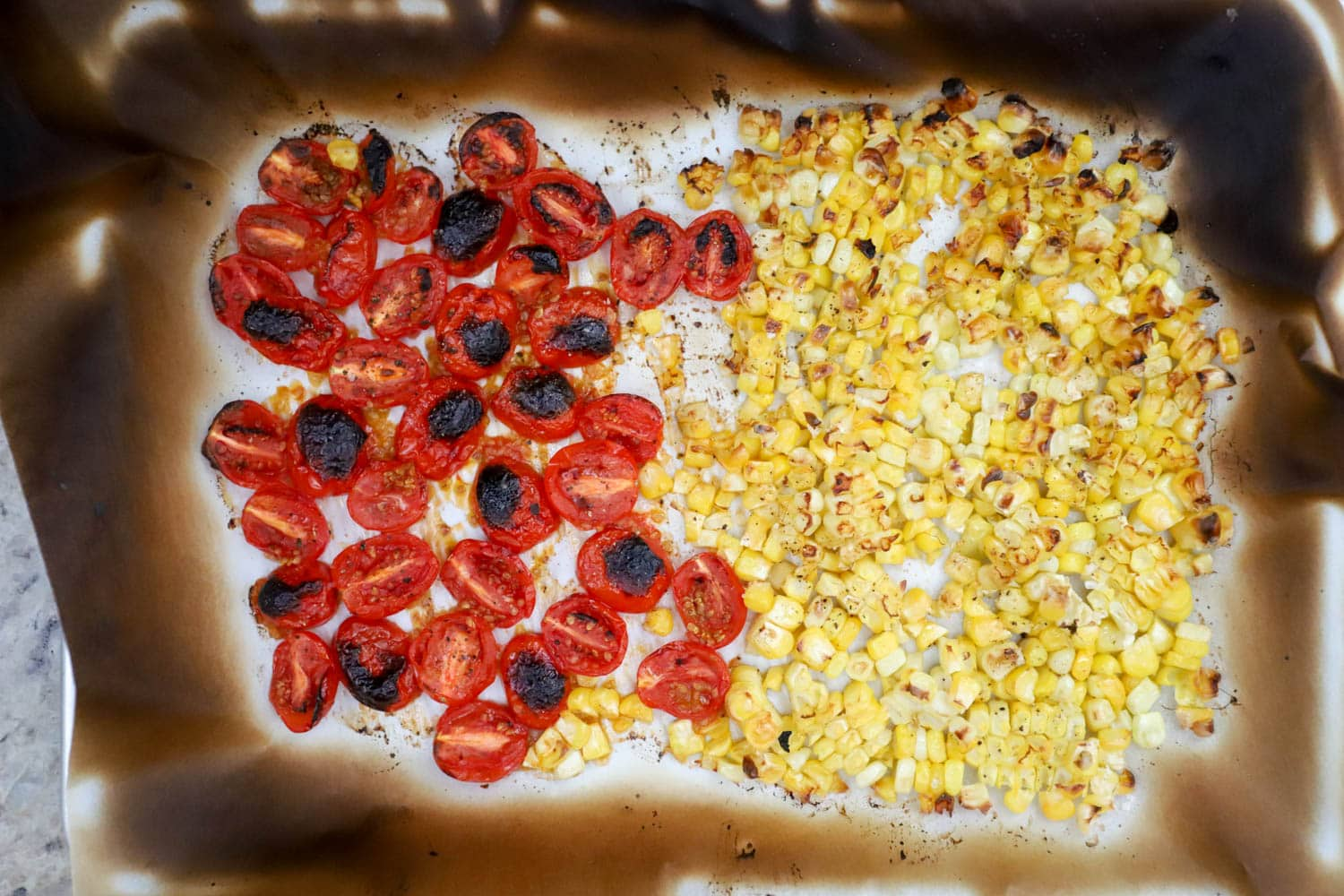 pan of broiled tomatoes and corn on charred parchment paper