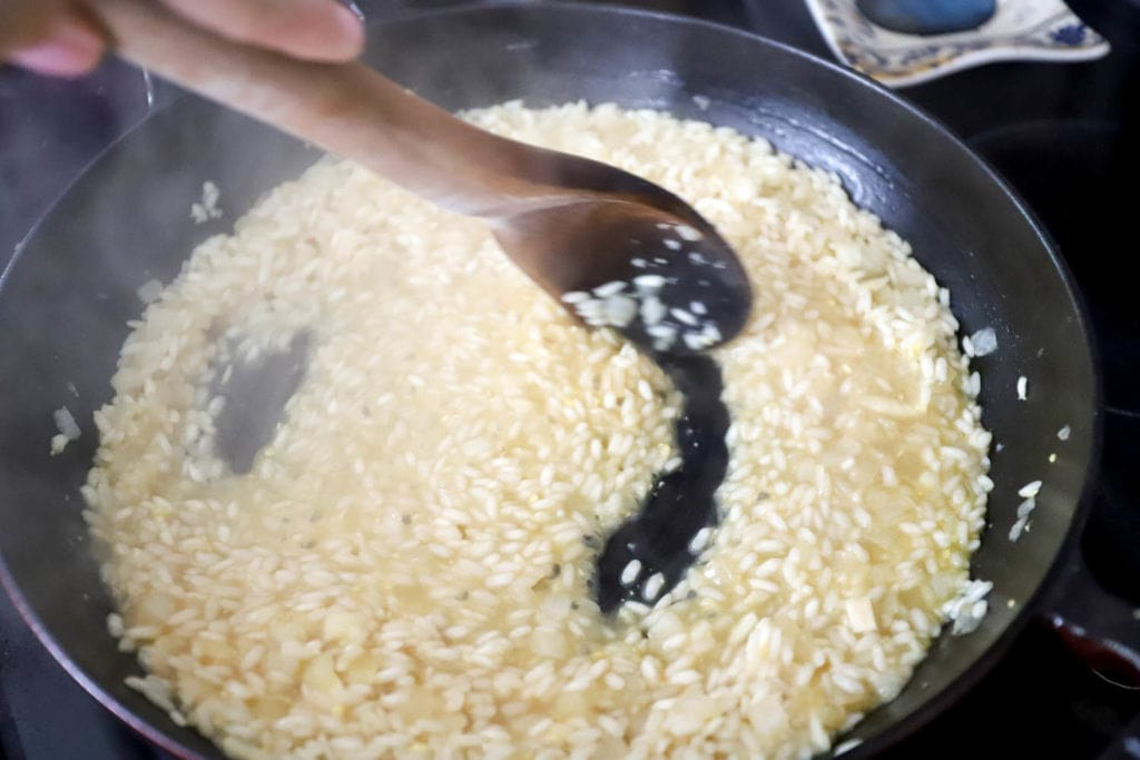 wooden spoon stirring risotto
