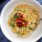 corn risotto bowl topped with green onions and blistered cherry tomatoes