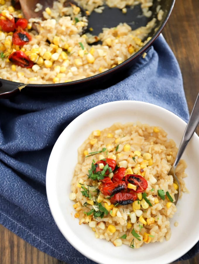 summer corn risotto with blistered cherry tomatoes in bowl