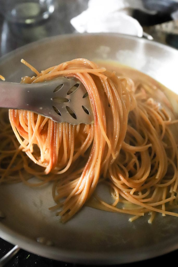 tossing pasta with tongs while cooking