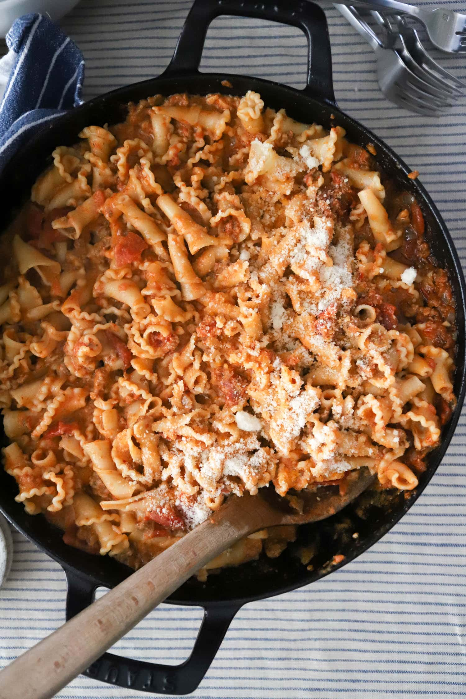 large skillet with pasta, spicy sausage vodka sauce, and parmesan cheese