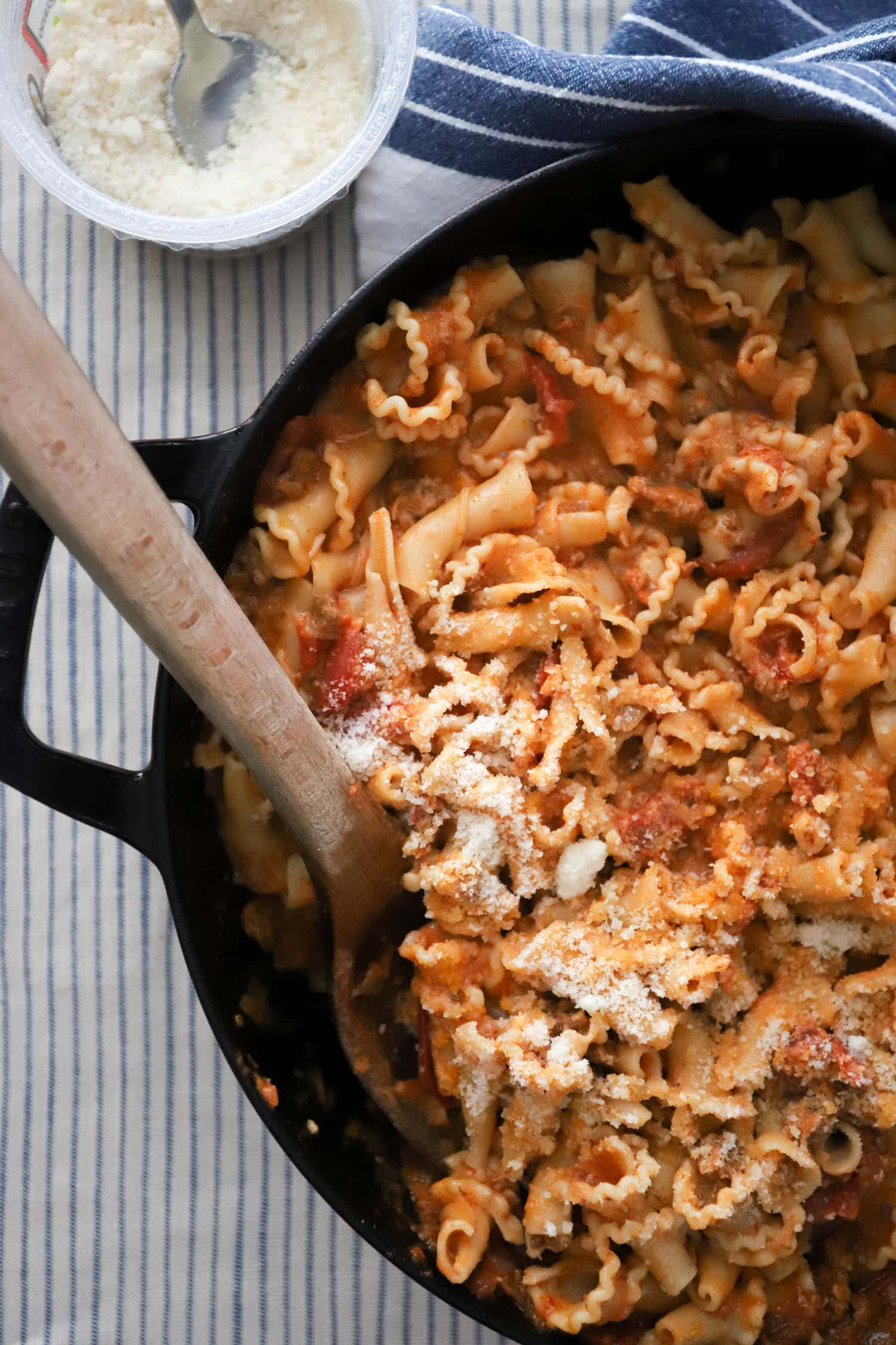 large skillet of curly pasta with parmesan and tomato sauce