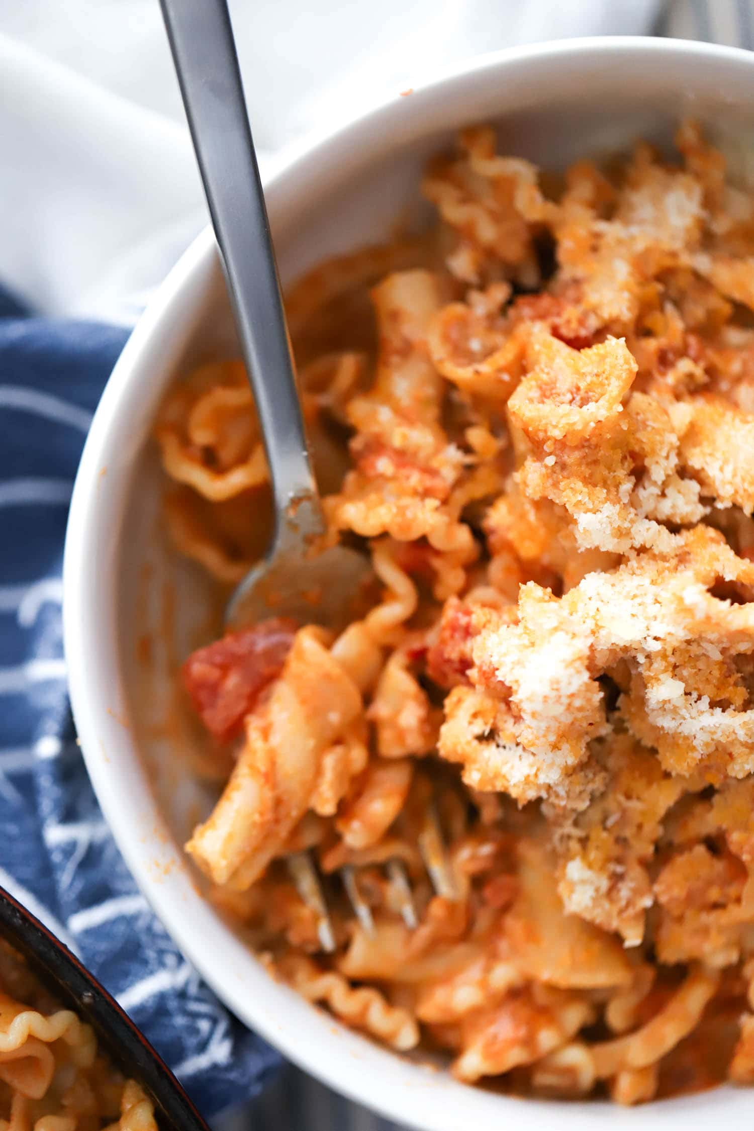 close up spoonful of vodka cream sauce with parmesan in bowl