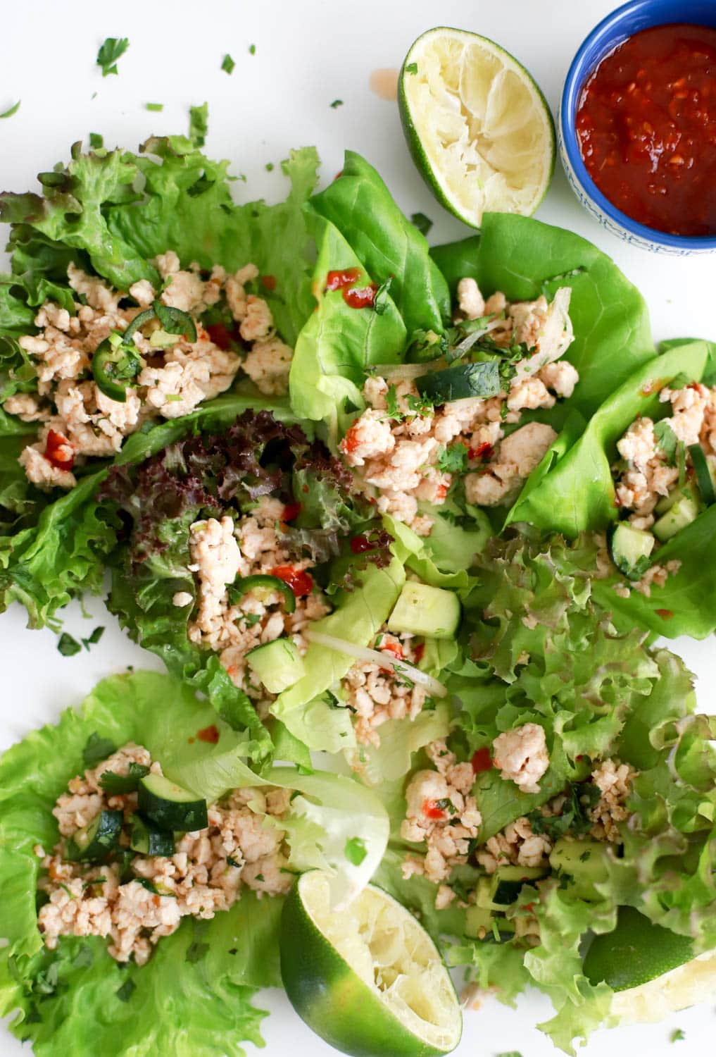 close up image of thai ground chicken lettuce wraps with lime wedges on the edge.