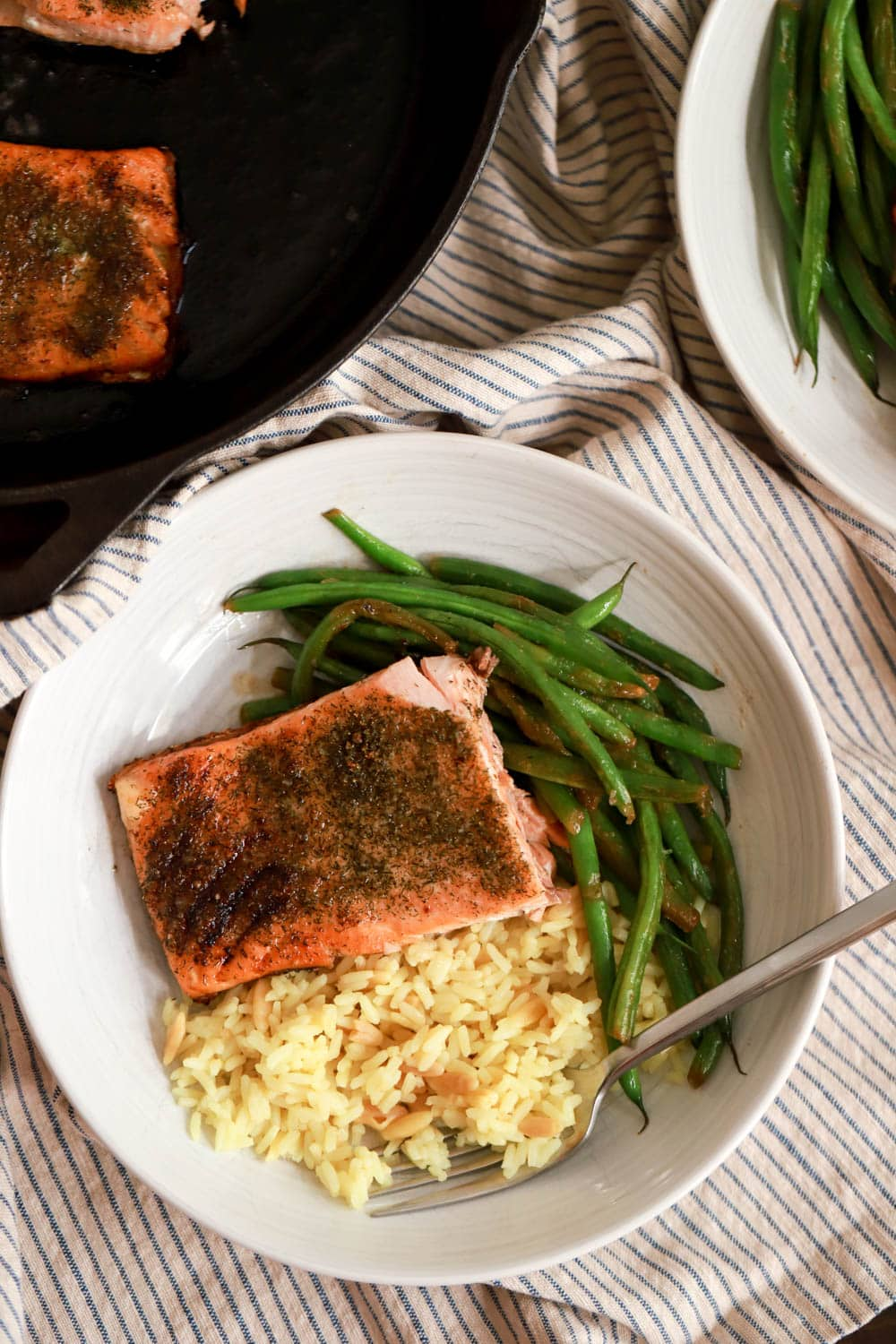 plate of pan seared salmon with rice and green beans on napkin
