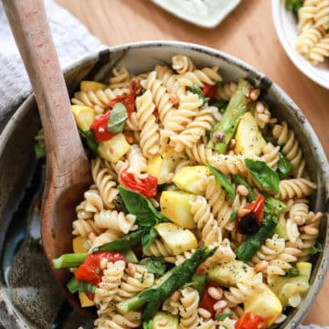 bowl of pasta salad with veggies and wooden spoon