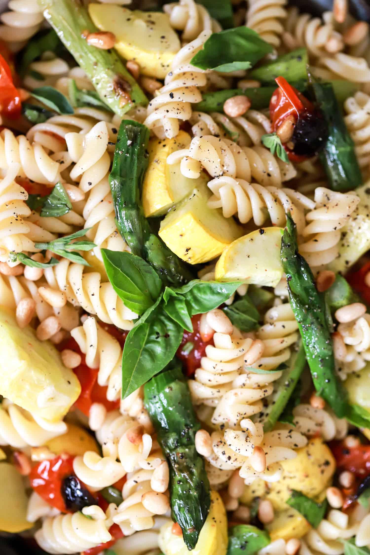 close up vegan pasta salad with asparagus and pine nuts