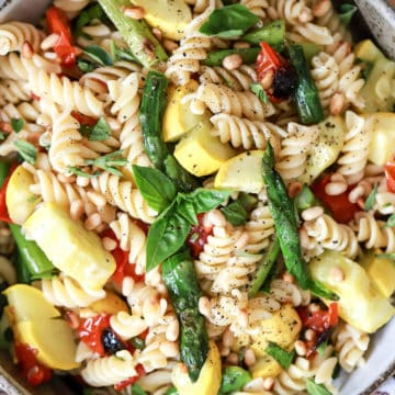 large serving bowl of vegan pasta salad with asparagus and tomatoes