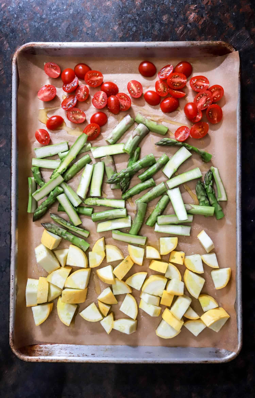 raw tomatoes asparagus and squash on sheet pan