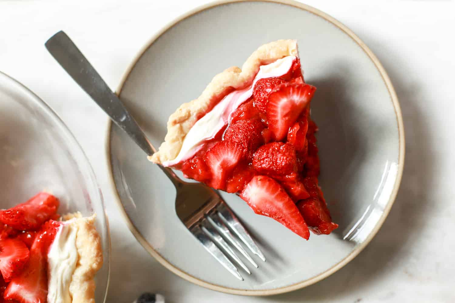 single slice of cream cheese strawberry pie with plate and fork